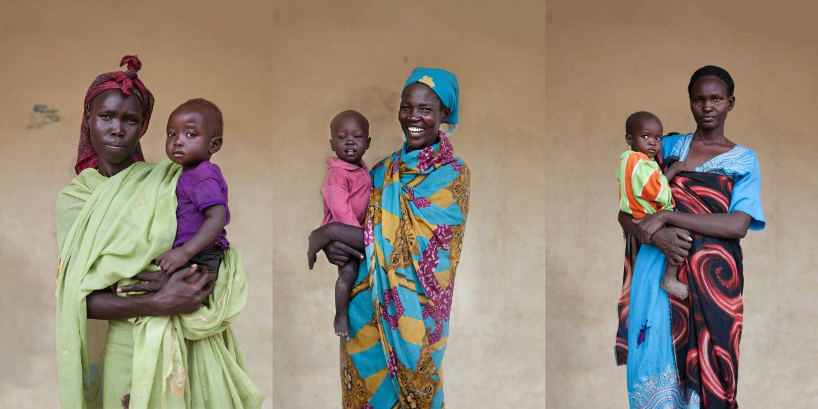 Three South Sudanese women with their infants outside of a maternal health clinic in rural South Sudan