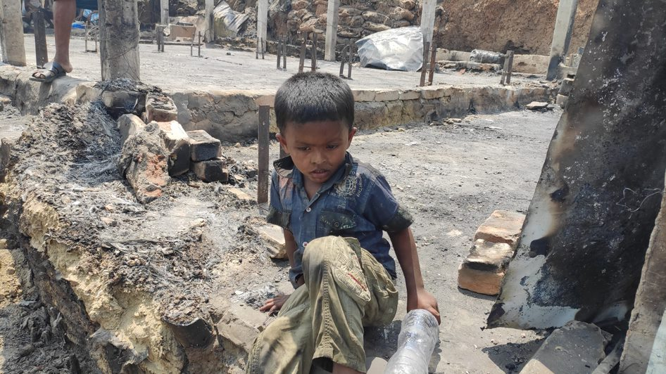 A young boy amid the wreckage of his home, destroyed on the March 22nd fire in Balukhali camp.