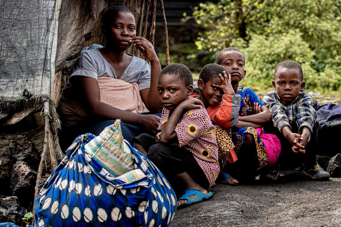 A Congolese woman and her five children sit in front of a small kitchen after being displaced by the eruption of Mount Nyiragongo, DRC, 2021